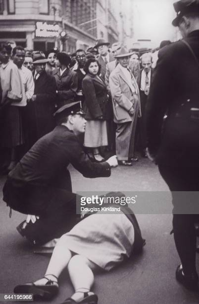 A throng of curious people surround a police officer crouching over a victim at a crime scene on a Manhattan street