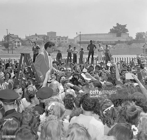 Throngs of fans surround singer and movie star Frank Sinatra for his autograph. Sinatra is on his way to Hollywood to make a movie.