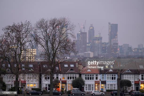 Through a gap of 100 year-old ash trees, Edwardian period homes bordering Ruskin Park in south London with residential high-rises at the distant Nine...