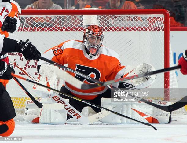 Through a maze of sticks Carter Hart of the Philadelphia Flyers keeps his eyes on the puck during the second period against the New Jersey Devils at...
