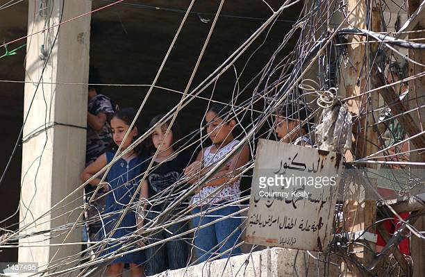 Through a tangle of electrical wires Palestinian children watch a Hamas demonstration in the Ain El Helweh Palestinian refugee camp September 29 2002...