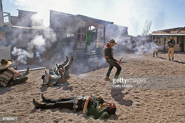 Through a thick layer of gunsmoke Tombstone marshals blow away 'Mexican' banditos as actors sprawl across the ground during a western scene performed...