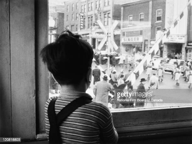 Through a window a young boy is watching a parade held in honour of the Annual Snowshoers' Convention Sherbrooke Quebec Canada 1958 Photo taken...