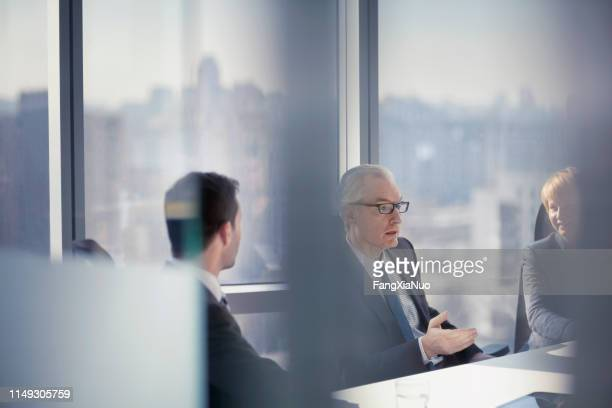 through the glass view of businessman talking to colleagues in conference room meeting - law stock pictures, royalty-free photos & images