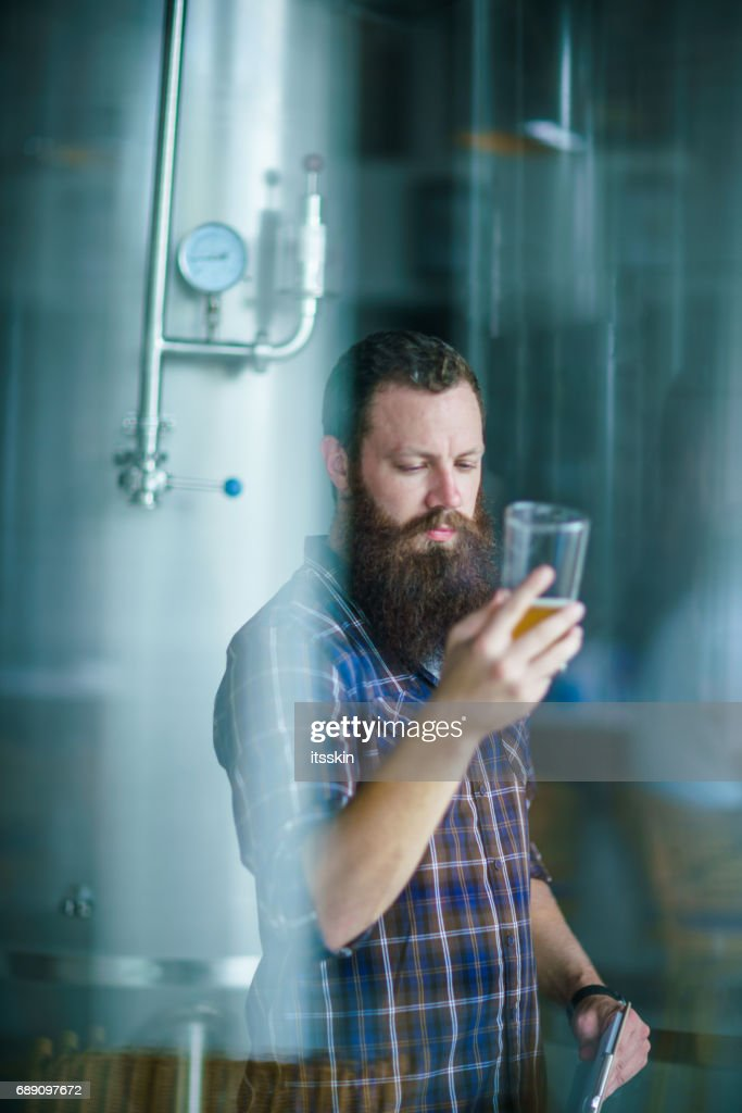 Through the window: master works in the brewery: beer testing, making remarks, quality control : Stock Photo