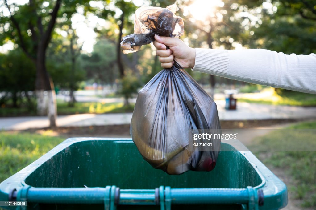 Throw the garbage bag into the trash can : Stock Photo
