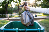 Throw the garbage bag into the trash can