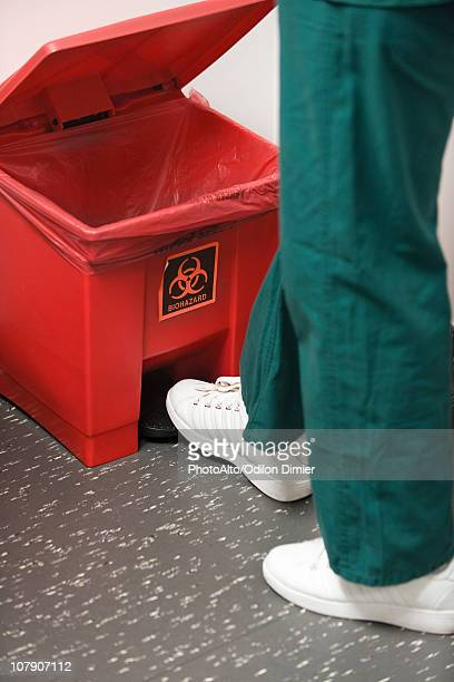 throwing away medical waste in biohazard garbage can - toxic waste stock pictures, royalty-free photos & images