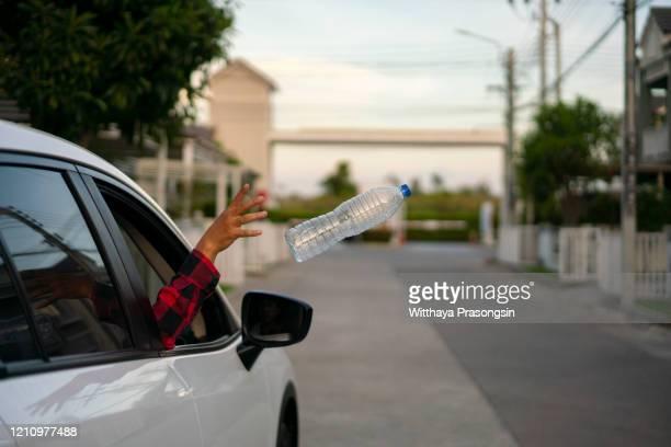 throwing bottle out car window - alleen één mid volwassen vrouw stockfoto's en -beelden