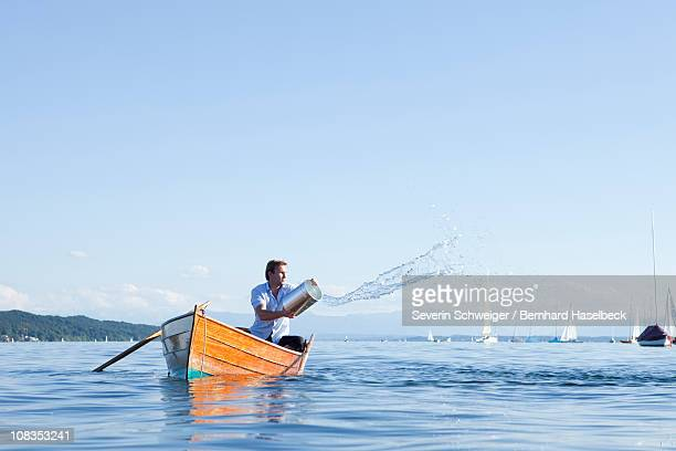 throwing buckets of water ot ouf boat - sinking stock pictures, royalty-free photos & images