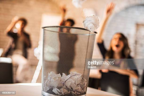throwing crumpled paper into a wastepaper basket. - garbage can stock photos and pictures
