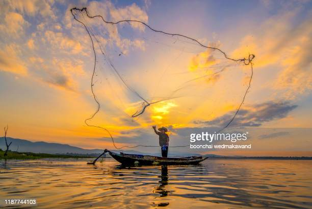 throwing fishing net during sunrise, thailand - folk music stock pictures, royalty-free photos & images