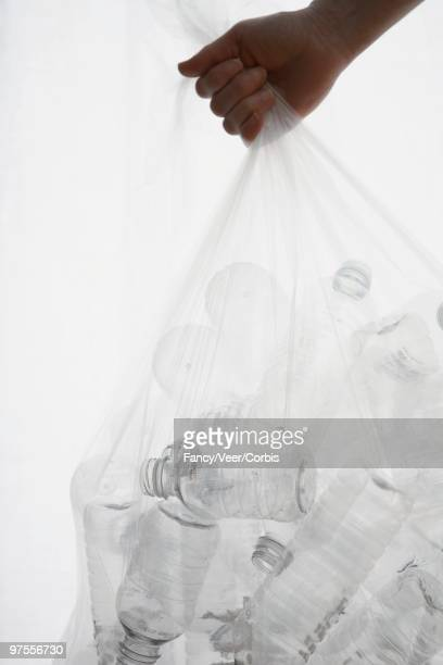 Throwing Out Trash Bag Full of Plastic Water Bottles