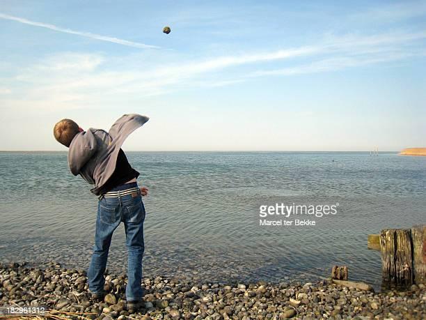 throwing rocks in the sea - solo un bambino maschio foto e immagini stock