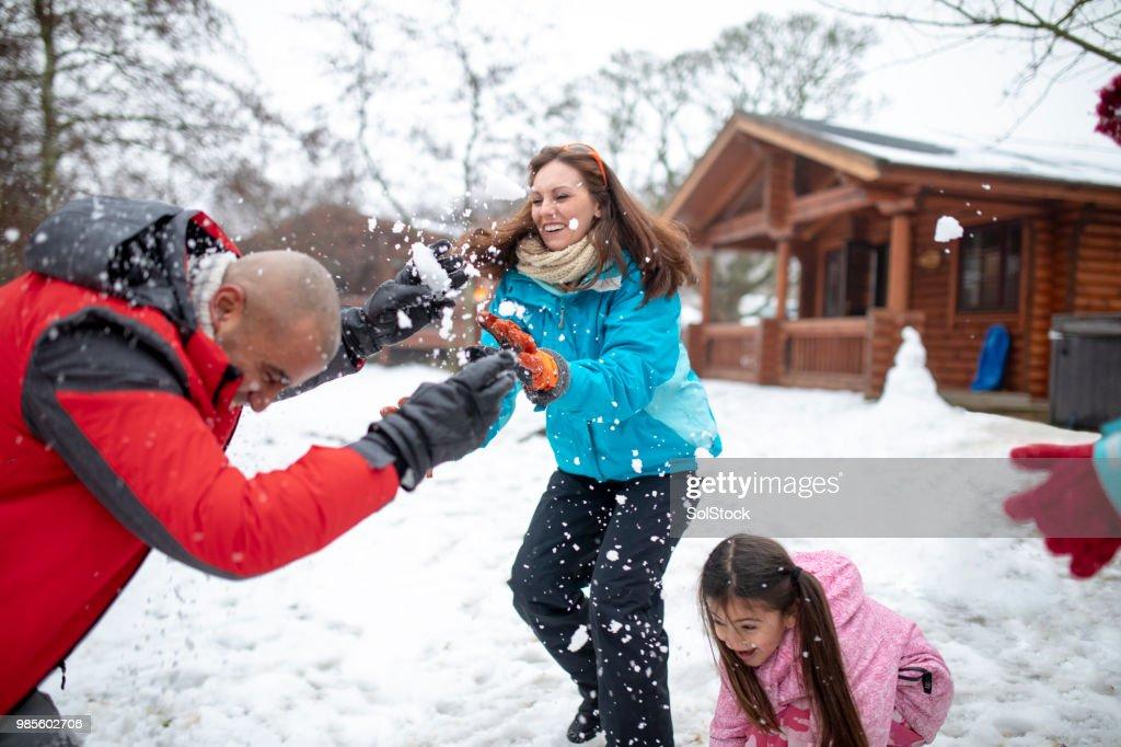 Jogando bolas de neve no seu marido : Foto de stock