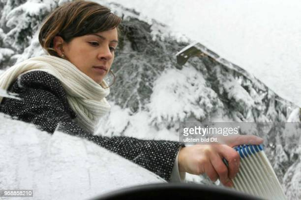 DEUTSCHLAND Thueringen Ilmenau Eine Frau entfernt das Eis von der Frontscheibe ihres Wagens
