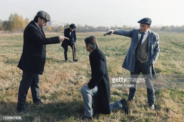 thug pointing weapon at back of head of detective. - dead gangster stock pictures, royalty-free photos & images