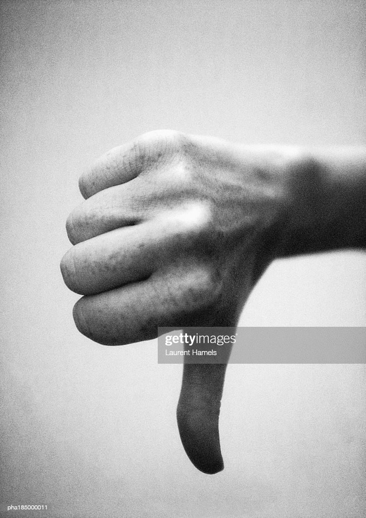 Thumb pointing down, close-up, b&w : Stockfoto