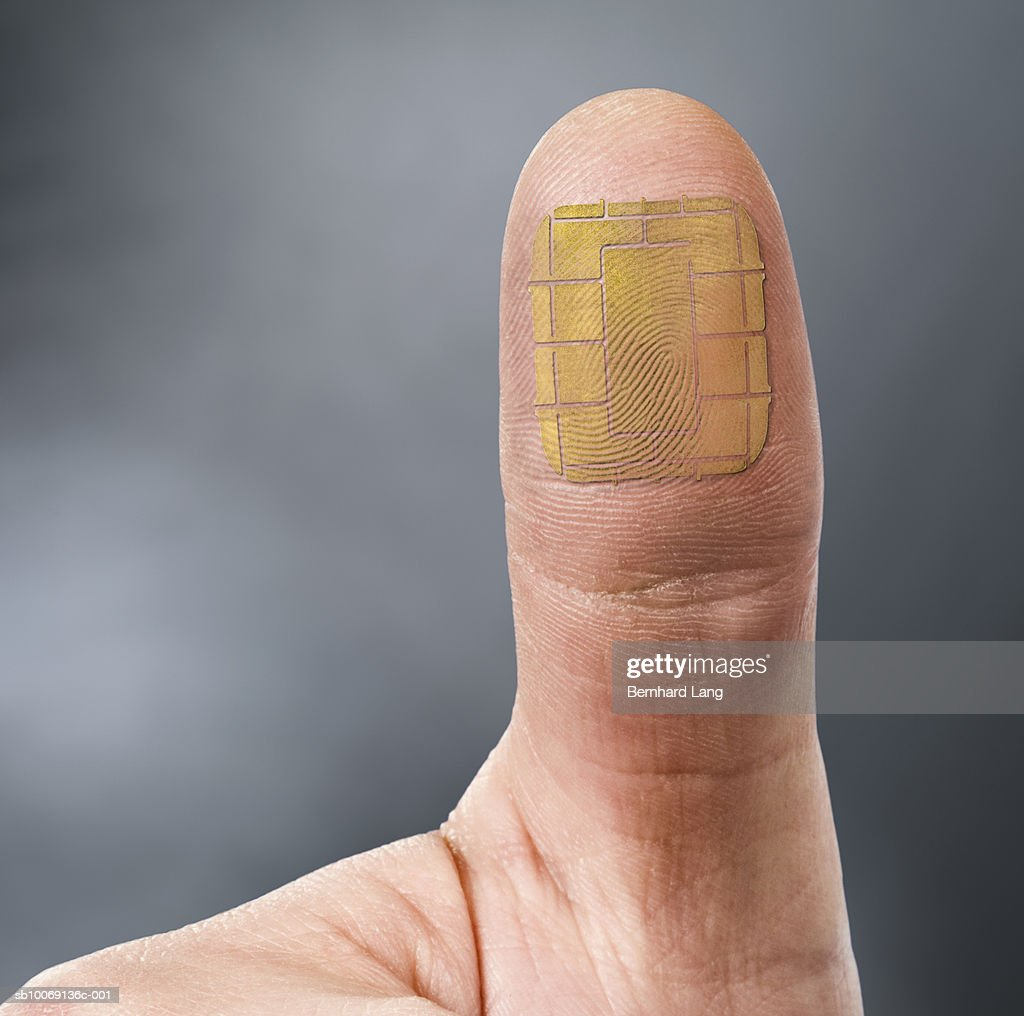 Thumb with computer chip, close-up (digital composite) : Stockfoto