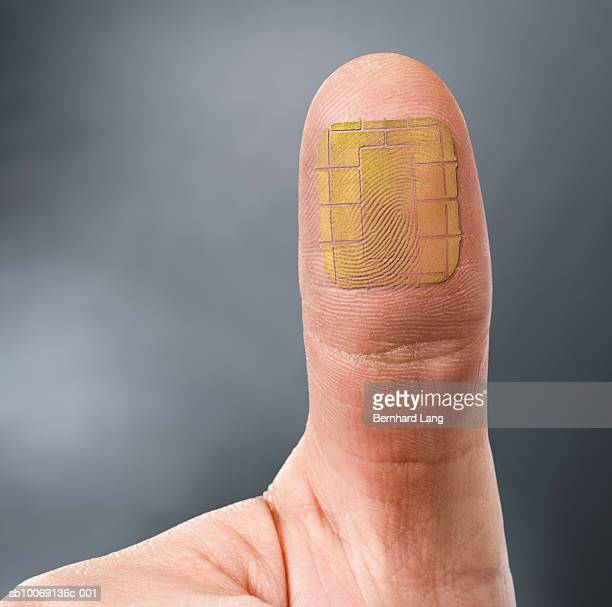 thumb with computer chip, close-up (digital composite) - 親指 ストックフォトと画像