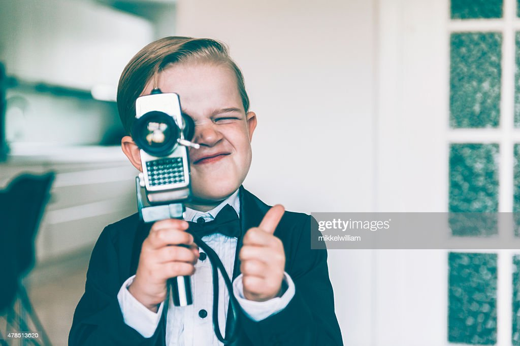 Thumbs up from boy shooting video with retro camera : Stock Photo