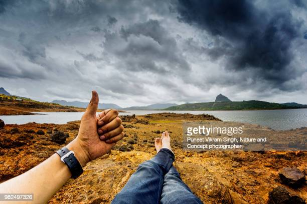 thumbs up in personal perspective at pawna lake - legs crossed at ankle stock pictures, royalty-free photos & images