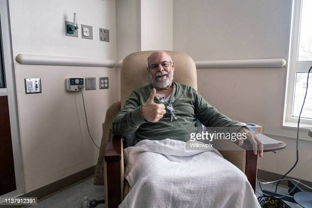thumbs up senior man cancer outpatient during chemotherapy iv infusion - iv infusion stock photos and pictures