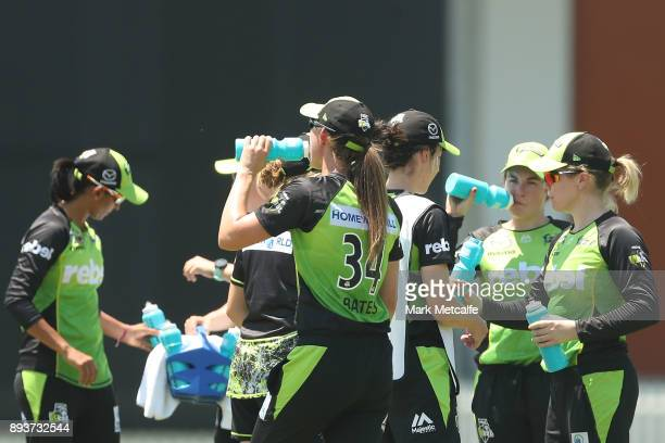 Thunder players drink water as the temperature soars towards 40 degrees during the Women's Big Bash League match between the Melbourne Stars and the...