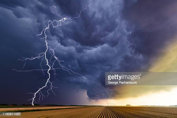 thunder striking over an agricultural field - tempesta foto e immagini stock