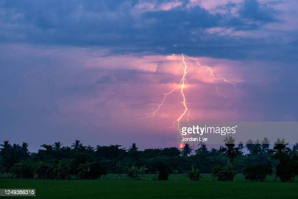 thunder striking over an agricultural field - 雷雨 ストックフォトと画像