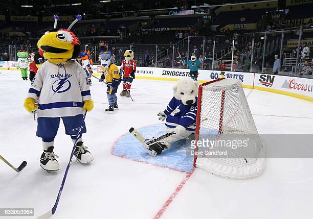 ThunderBug of the Tampa Bay Lightning looks on as Carlton the Bear of the Toronto Maple Leafs looks at the puck in the net during the mascot showdown...