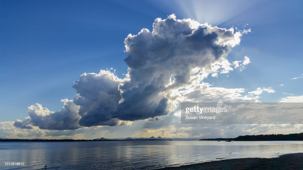 Thundercloud over Pumicestone Passage from Bribie Island in Queensland Australia looking over water toward the Glasshouse mountains : Stock Photo