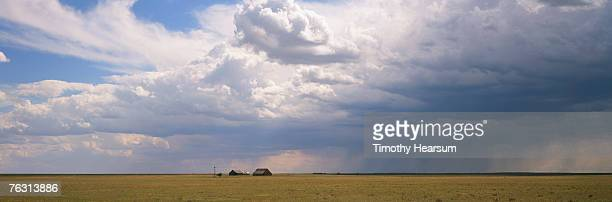 thunderhead clouds over two old barns and field - timothy hearsum stockfoto's en -beelden