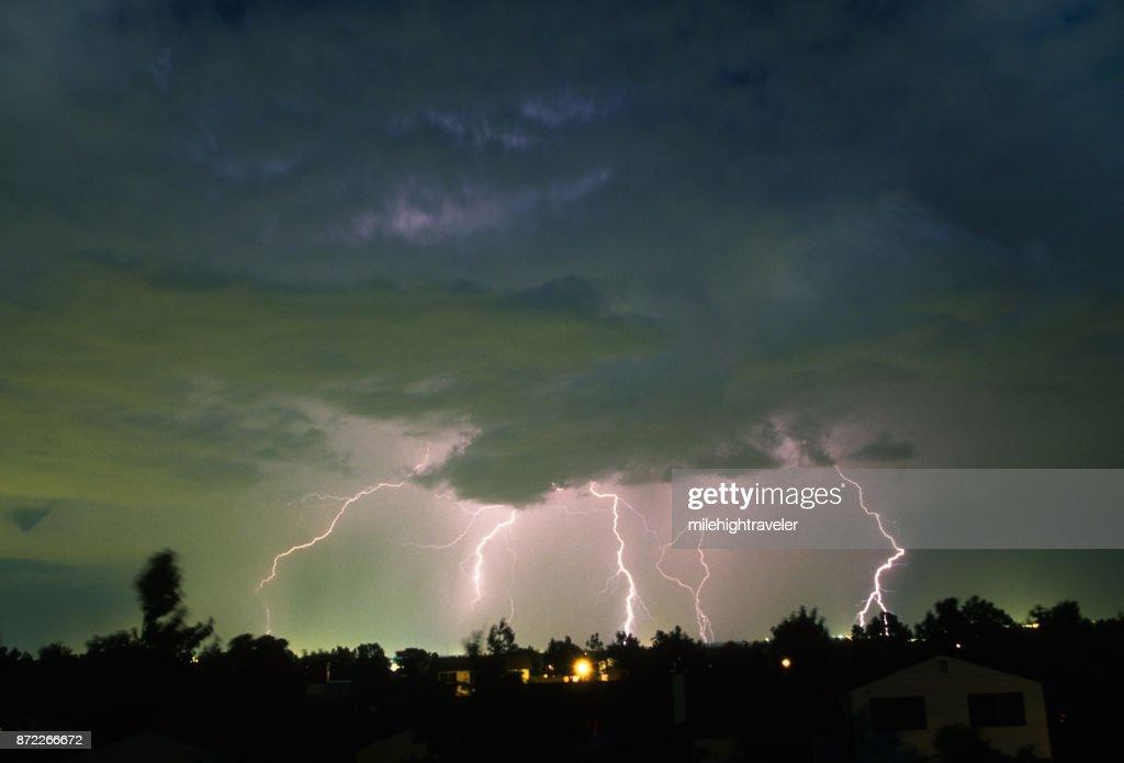 Thunderhead lightning bolts strikes over Denver Colorado neighborhood homes : Stock Photo