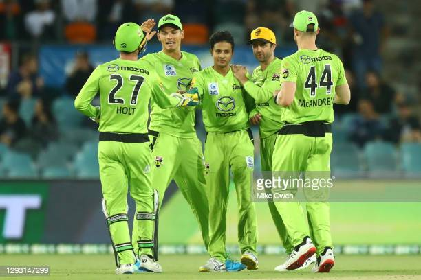Thunders players celebrate around Tanveer Sangha of the Thunder after winning the Big Bash League match between the Sydney Thunder and the Melbourne...