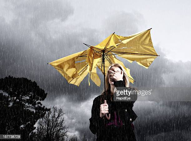 Thunderstorm gets the better of umbrella and woman holding it
