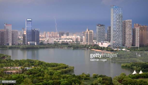 Thunderstorm over Hefei city skyline, lightning strikes building in the distance, China