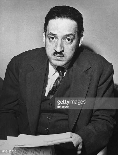 Thurgood Marshall attorney for the NAACP seated holding a paper