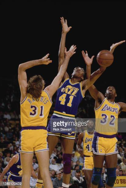 Thurl Bailey, Power Forward for the Utah Jazz, Magic Johnson and Kurt Rambis of the Los Angeles Lakers jump for the basketball during their NBA...
