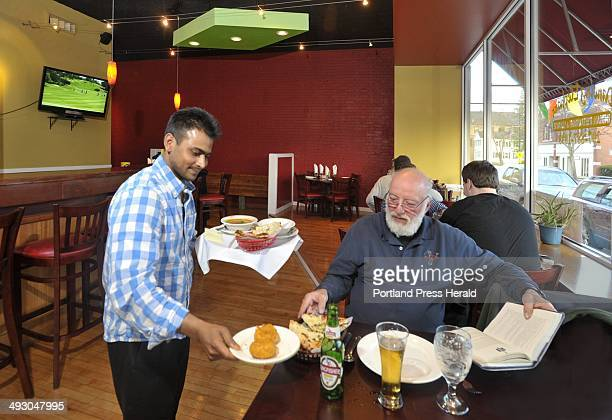 Thursday April 19 2012 Dine Out Maine art from the Dancing Elephant restaurant at 855 Main St Westbrook Owner Iqubal Hossain delivers food to Gary...