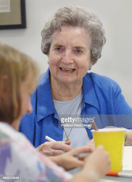 Adele Robinson a resident of Falmouth House at Ocean View talks with visitor Jayde Bazinet as they decorate note cards that will be sold at Books Etc...