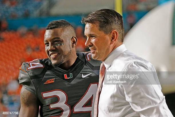 Thurston Armbrister is greeted by Head coach Al Golden of the Miami Hurricanes as part of the senior night ceremonies prior to the game against the...