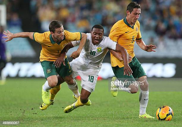 Thuso Phala of South Africa is challenged by Tommy Oar and Mark Milligan of the Socceroos during the International Friendly match between the...