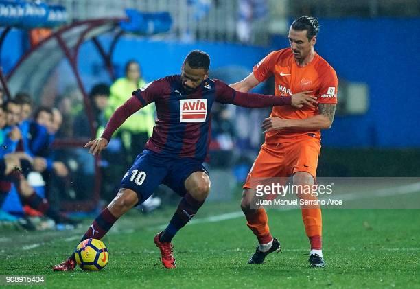 Tiago Manuel Dias Correia 'Bebe' of SD Eibar duels for the ball with Zdravko Kuzmanovic of Malaga CF during the La Liga match between SD Eibar and...