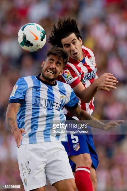 Tiago Mendes of Atletico de Madrid wins the header before Samuel Garcia Sanchez of Malaga CF during the La Liga match between Club Atletico de Madrid...