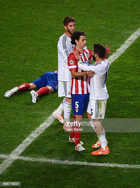 Tiago of Club Atletico de Madrid clashes with Daniel Carvajal and Sergio Ramos of Real Madrid during the UEFA Champions League Final between Real...
