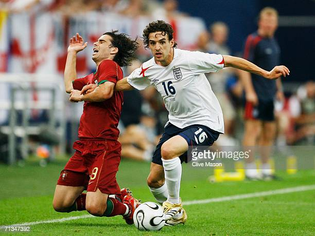 Tiago of Portugal falls to the ground as Owen Hargreaves of England surges forward during the FIFA World Cup Germany 2006 Quarterfinal match between...