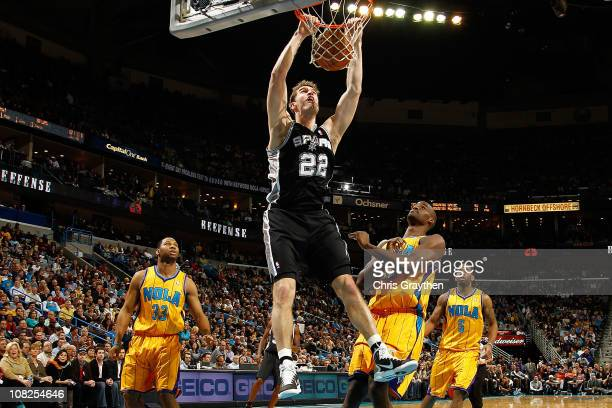 Tiago Splitter of the San Antonio Spurs dunks the ball over Emeka Okafor of the New Orleans Hornets at the New Orleans Arena on January 22 2011 in...