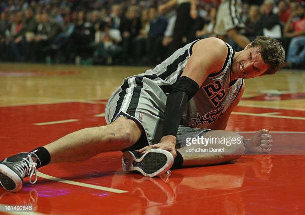 Tiago Splitter of the San Antonio Spurs winces after injuring his ankle against the Chicago Bulls at the United Center on February 11 2013 in Chicago...