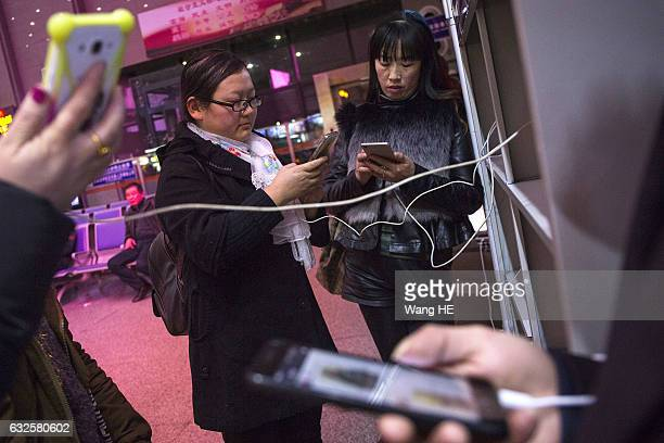 Tian Bifang charging iphone in public charging station at Wuchang train station on January 14 2017 in Wuhan China The 22yearold Tian Bifang packed up...